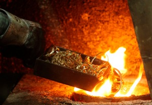 A worker places gold jewellery into a melting furnace at the Austrian Gold and Silver Separating Plant 'Oegussa' in Vienna